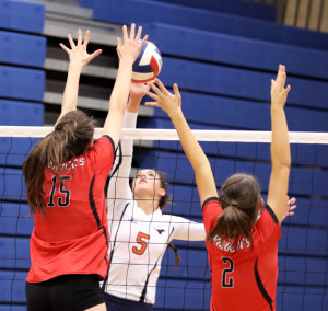 Kaitlyn Coffey spikes the ball between a pair of Lake Highlands defenders.