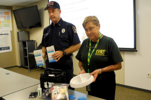 Sachse Fire Lt. James Marple and Sachse CERT Director Jeri McGrath display one of the pet 72 hour emergency pet safety kits.