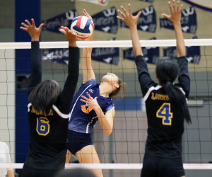 Joe Diehl/The Sachse News Kaitlyn Coffey attempts to spike the ball between a pair of Lakeview Centennial defenders.