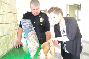 Lt. Steve Norris shows Sachse resident Kristin Poligala how to use the Drug Take back box in the Police Department lobby.