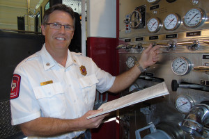 Patty Montagno/The Chief Martin Wade checks the valve readings on one of the fire trucks.