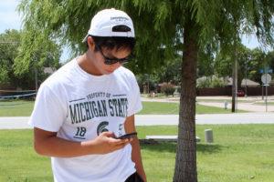 "Sachse's Brandon Lam, 15, checks for his next ""Pokestop"" on his telephone."